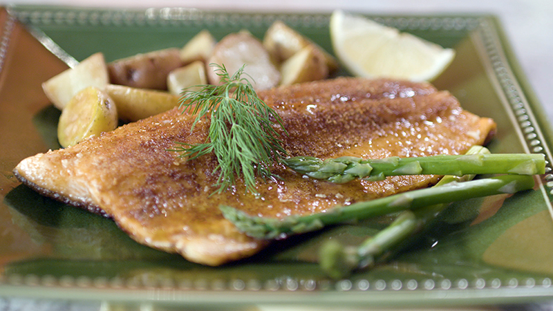 This is a photograph of seared fish accented by asparagus, lemon, potatoes and dill on a green plate.